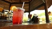 Um bar com uma bebida que contém uma cereja e uma fatia de laranja