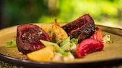 Carne de res especiada y asada con apio, frutas y papas