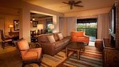Un coin salon avec un grand canapé-lit, table basse, 2fauteuils et une armoire avec téléviseur