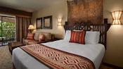 Un lit avec une tête de lit grossièrement sculptée, 2appliques murales, décoration murale, canapé , table basse et balcon