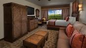 Une armoire, commode, TV à écran plat, miroir, table et 2chaises, balcon, lit, canapé et table basse