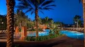 La piscine Samawati Springs entourée de palmiers le soir