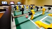 Gros plan sur une table de baby-foot avec des bonshommes noirs et jaunes