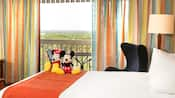 A room with a view, a bed with a Mickey and Minnie plush, an outdoor patio balcony with a table and chairs, another chair and a lamp