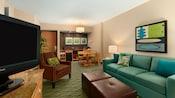 Um quarto com um sofá, cadeiras, TV, área de jantar, cozinha compacta e quadros nas paredes