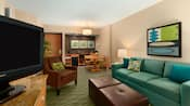 A room with a couch, chairs, TV, dining area, kitchenette and artwork on the walls