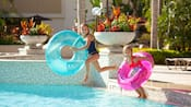 2 girls with inner tubes jumping into a pool