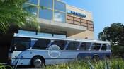 """Un edificio con un letrero que dice """"Wyndham"""", cerca de un autobús con un letrero que dice """"Disney Springs Resort Area Hotels"""""""