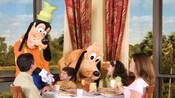 Goofy y Pluto comparten con una familia en un restaurante