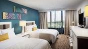 Una habitación con 2camas, 3lámparas, 2cuadros, un espejo, un TV, una silla y cortinas