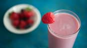 A smoothie with a raspberry garnishing the glass near a bowl of berries