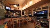 Un bar con mesas cerca de una televisor y un pez espada relleno con una mesa de pícnic y un faro al aire libre en las cercanías