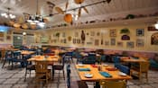 Restaurante con mesas preparadas y una fila de ventiladores de techo