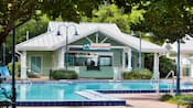 A pool near a bar with a sign that reads Turtle Shack Poolside Snacks