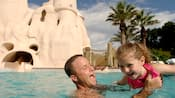 Pai brinca alegremente com a filha na Sandcastle Pool, no Disney's Old Key West Resort