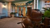 Un timón de barco antiguo y una columna de dirección en la parte exterior de Olivia's café