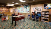 A Community Hall with foosball, video monitors, air hockey and shelves of games and toys