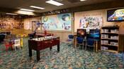 Uma área de uso comum com pebolim, monitores de vídeo, hóquei de mesa e prateleiras de jogos e brinquedos