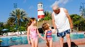 Un abuelo con sus dos nietas junto a una piscina en Disney's Old Key West Resort