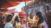 Una familia come en la mesa mientras una camarera sostiene una bandeja de comida