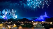 Fireworks burst in the sky above Cinderella Castle and Space Mountain