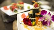 Sushi piled on a plate next to flowers