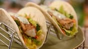 2 fish tacos with lettuce, peppers, carrots and tartar sauce