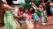 A small girl wearing a lei and grass skirt smiles as hula dancers teach her family the hula dance