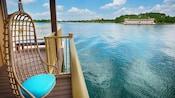 Una silla de mimbre colgante en la terraza de un bungalow sobre el agua, con vista al agua y al Hotel