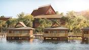 Tres bungalows junto al agua con palmeras en el fondo