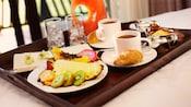 Fatias de abacaxi, pitaia, mamão, kiwi, goiaba, lichia e fortunella perto de 2xícaras de café, 2croissants, um açucareiro, leite, 2copos com gelo e uma jarra de suco em uma bandeja.