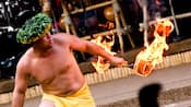 A fire dancer with a flaming baton