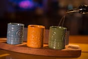 Liquer is poured into 3 cups with the words Trader Sam's Grog Grotto emblazoned on a cup