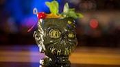 Drinque em uma caneca estilizada como uma cabeça encolhida sorridente
