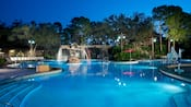 An illuminated swimming pool featuring an ornate fountain glimmering beneath a moonlit Florida sky