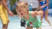El agua salpica mientras una joven Visitante disfruta de la piscina en Disney's Port Orleans Resort