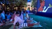 No gramado à noite, um home e seu filho estão entre as famílias que assistem à Princesa e o Sapo