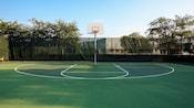 Un aro de baloncesto en una gran cancha verde con vallas