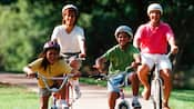 Family of 4 wearing helmets riding bikes down a tree-lined lane