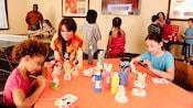 Un membre de l'équipe surveillant 2enfants en train de peindre des figurines Disney sur une table d'art plastique