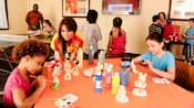 Cast Member watching as 2 kids at a crafts table paint Disney figurines