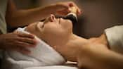 A relaxed woman wrapped in towels at a resort spa receives a facial