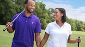 A man and woman walking on a golf course, each holding one golf club