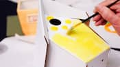 A brush held by a Guest painting a cardboard birdhouse yellow