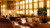 Uma mesa, sofá e cadeiras em uma sala de estar ensolarada ao lado de várias janelas