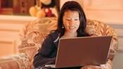 Um hóspede, sentado em uma cadeira estofada, usa um laptop para acessar a internet