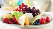Un plato con diferentes tipos de quesos maridados con fresas, arándanos azules, rodajas de melón, uvas y frambuesas