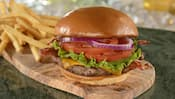 Una hamburguesa de carne de res con queso, tocineta, lechuga, rodajas de tomate, cebollas moradas y queso cheddar, cerca de una pila de papas fritas
