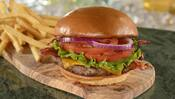 A cheeseburger filled with a meat patty, bacon, lettuce, tomato slices, purple onions and cheddar cheese near a pile of French fries
