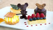 A pastry topped with blueberries and raspberries near a chocolate topped pastry, a rounded pastry topped by a chocolate, a triangular pastry and a chocolate figurine of Mickey Mouse